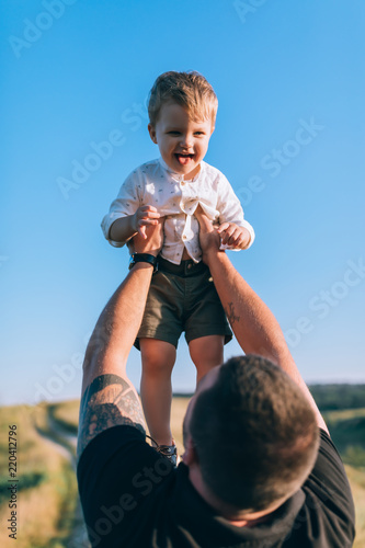 young father throwing up adorable smiling little son against blue sky Wall mural