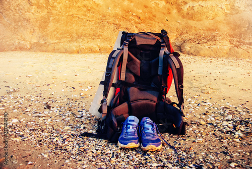 Tourist backpack and sneakers on the sea coast in summer on a sunny morning 9d833850c97d9