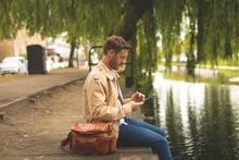 Man Using Digital Tablet While Sitting Near Lake Side