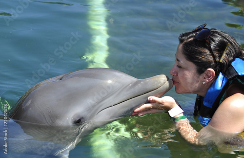 Woman holding and getting a kiss from a dolphin.