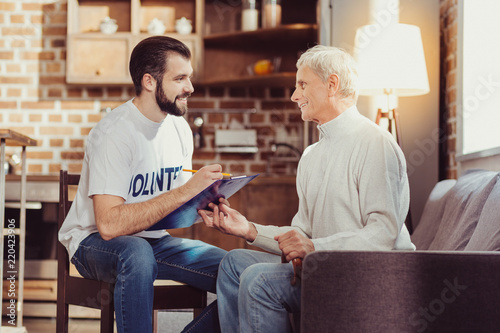 Important information: Attentive pleasant clever man sitting in the bright room on the chair looking at retired and making notes Wallpaper Mural