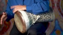 Playing Fast Rhythm On Clay Doumbek With Fish Skin Head.
