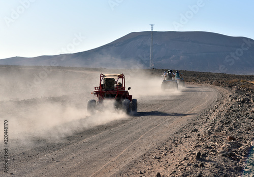 Fuerteventura, Canary Islands, North Africa, Spain: a dune buggy on the dirt and winding road on the cliff to Playa de Cofete beach