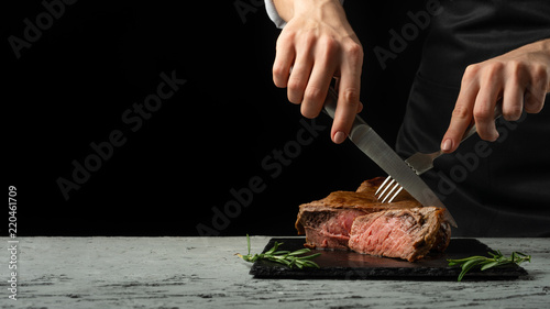 Montage in der Fensternische Steakhouse Chef, cut with a meat steak on a black background with an open space for text or restaurant menus. Horizontal photo Black text area.