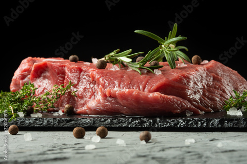 Keuken foto achterwand Vlees Raw fillet of beef steak with rosemary, thyme, and spices on a blackboard.Macro