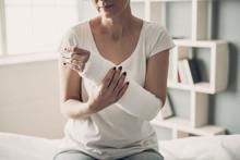Close-up Of Female Broken Arm In Plaster Cast