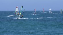 Group Of Windsurfers Sail Back A Forth Over Choppy Sea.