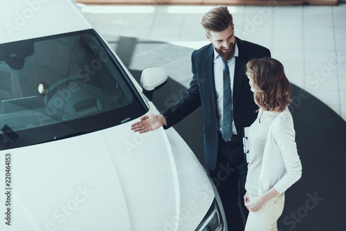 Car Salesman Showing Car to Woman in Showroom