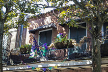 Traditional Brick Colonial Home With A Mardi Gras Flag And Decorations On The Balcony In The French Quarter In New Orleans, Louisiana, USA