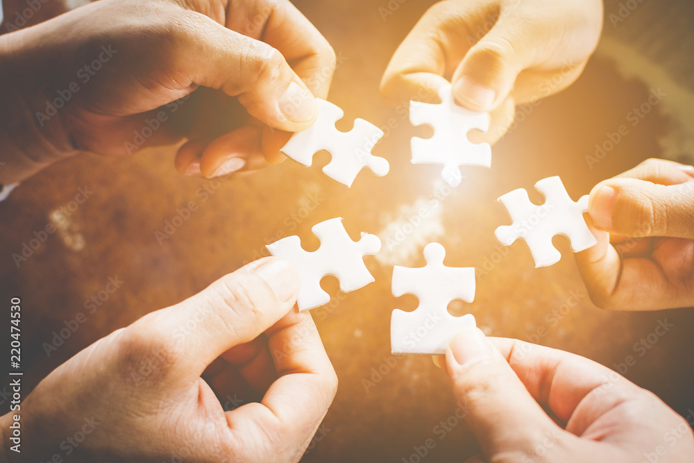 Fototapeta Hand of diverse people connecting jigsaw puzzle. Concept of partnership and teamwork in business