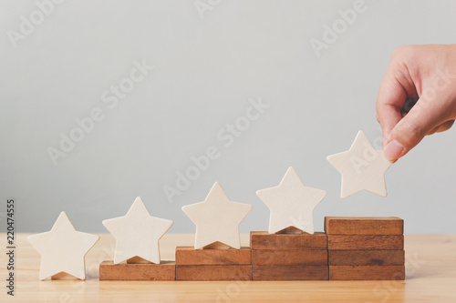 Obraz Hand putting wooden five star shape on table. The best excellent business services rating customer experience concept - fototapety do salonu