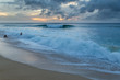 People playing on the beach with big waves on the north shore of Oahu, Hawaii