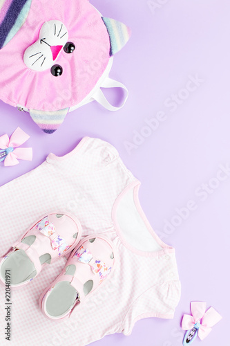 ff3980307685 Little girl clothes collection flat lay with t-shirt, jeans, sandals,  backpack on pastel background.