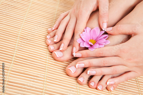 Tuinposter Pedicure Care for beautiful woman skin and nails. Pedicure and manicure at beauty salon. Woman legs, hands with flower on bamboo. Spa therapy. Closeup photo of female feet with white french manicure, pedicure