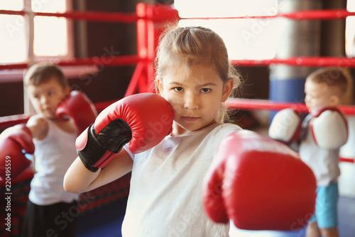 Valokuvatapetti Little girl in boxing gloves on ring