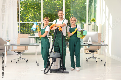 Fotografía  Team of janitors with cleaning supplies in office