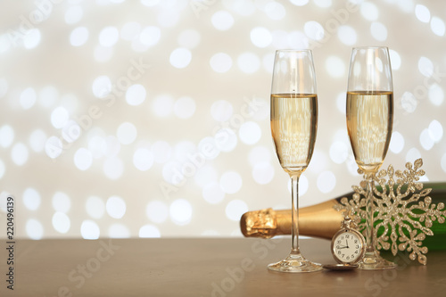New year composition with champagne and space for text against blurred Christmas lights
