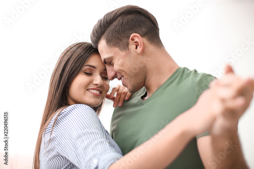 Obraz na plátně  Beautiful young couple dancing on light background