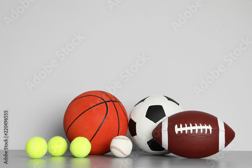 Photo Different sport balls on table against color background