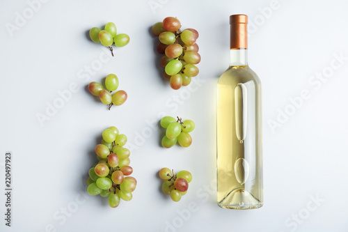 Bottle with white wine and fresh ripe juicy grapes on light background, top view