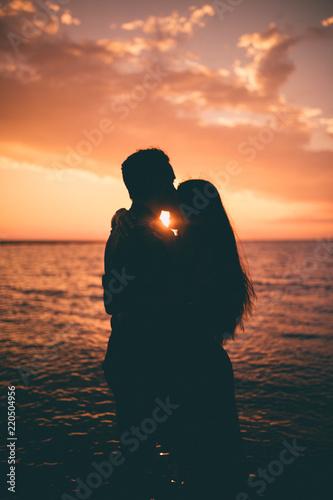 Valokuvatapetti Giovane coppia di ragazzo e ragazza si baciano abbracciandosi di fronte al tramonto rosso fuoco in riva al mare sulla spiaggia