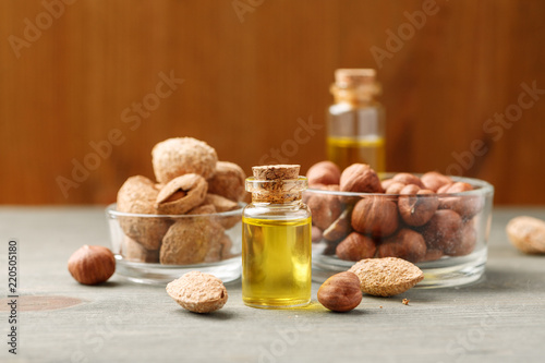 Almond and hazelnut in glass bowls with bright oil in small vial with wooden cork
