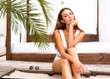 canvas print picture - fashion girl in a swimsuit sits on the beach in tropical palms