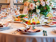 Table Served For Wedding Banquet With Cutlery And Flowers In Vases. Salads, Appetizers And Glasses With Wine.