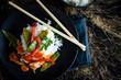 Reisgericht mit Gemüse und Fleisch auf schwarzem Teller