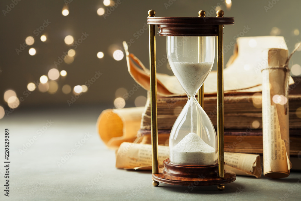 Fototapety, obrazy: Sand running through the hourglass and old vintage books. Time keeper concept.