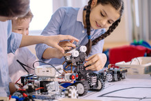 Excited Little Kid And Two Smiling Teen Friends Construct Robotic Toys While Playing During Their Leisure Time In Technical Workshop. Intelligent Activity.