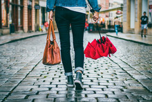 Woman Holding Leather Bag And Red Umbrella And She Is Walking On The Street After Rain