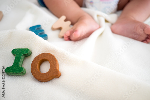 Fotografía  IQ text wooden word on blanket with blurred kid foot and copy space background,