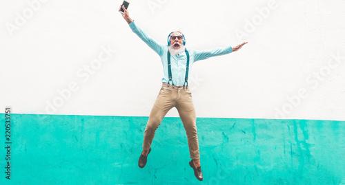 Senior crazy man jumping and listening music outdoor - 220533751