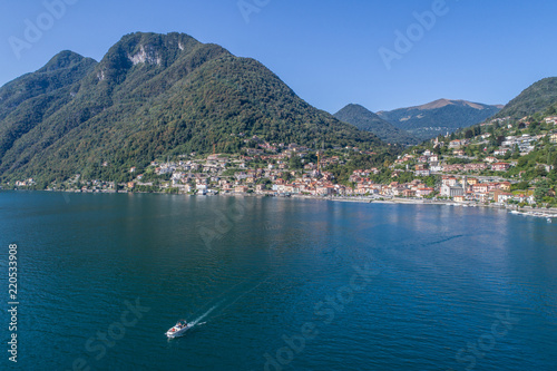 Lake of Como, boat on the lake and village of Argegno Wallpaper Mural
