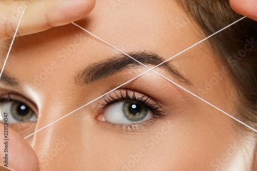 Eyebrow threading - epilation procedure for brow shape correction Canvas Print