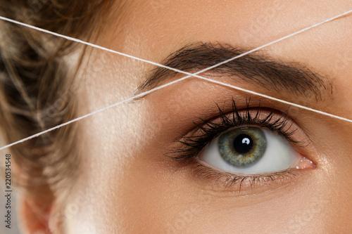 Fotografiet  Eyebrow threading - epilation procedure for brow shape correction