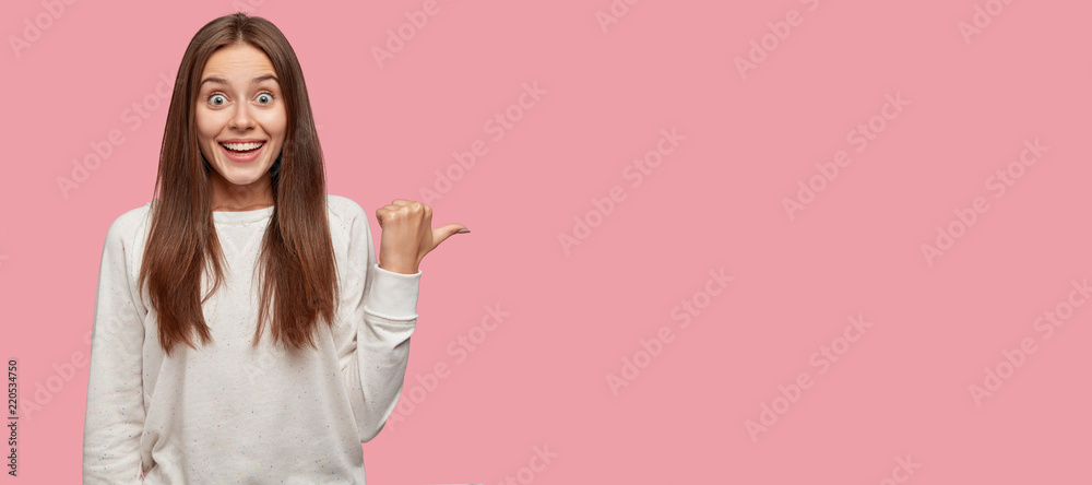 Fototapety, obrazy: Horizontal portrait of amazed beautiful happy lady dressed in casual clothes, points with thumb at free space, suggests you visit this place, isolated over pink background. Advertisement concept
