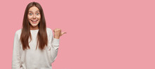 Horizontal Portrait Of Amazed Beautiful Happy Lady Dressed In Casual Clothes, Points With Thumb At Free Space, Suggests You Visit This Place, Isolated Over Pink Background. Advertisement Concept