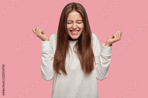 Successful brunette girl closes eyes from happiness, keeps raised fists, dressed casually, celebrates her victory with triumph, isolated over pink background. People, joy, body language concept