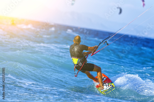 Man kitesurfer riding the waves with strong winds. Bright Sunny day.
