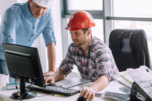 Young Ambitious Constructor With His Partner Are Doing The Model Of Building On The Computer. Engineer Is Good At Computers
