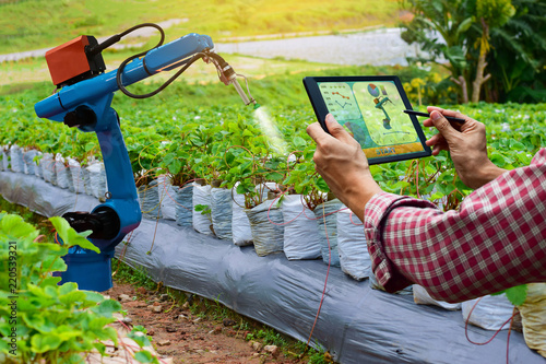 Photo  Farmer holding a tablet smart arm robot work agricultural machinery technology