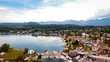 Aerial drone view panoramic Velden Am Worthersee lake, Austria day sunny mountain view