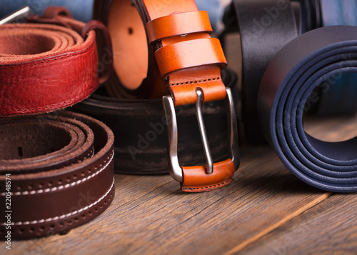 Fotografia  Collection of leather belts on a wooden table