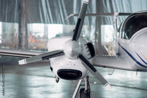 Valokuva  Propeller airplane in hangar, plane on inspection