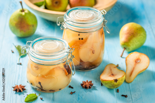 Sweet and tasty pickled pears on blue table