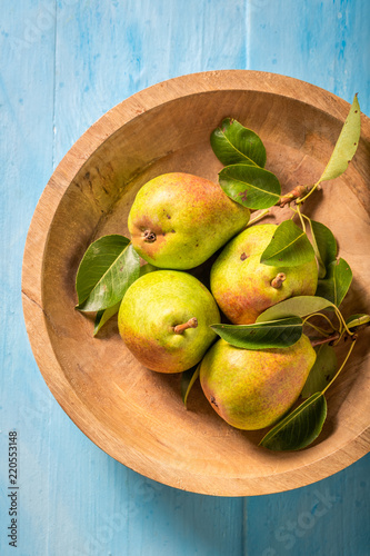 Sweet pears on the wooden bowl and blue table