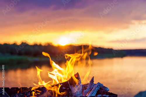 bonfire by the river at sunset Fototapeta