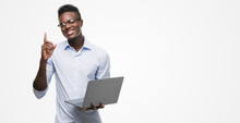 Young African American Businessman Using Computer Laptop Surprised With An Idea Or Question Pointing Finger With Happy Face, Number One